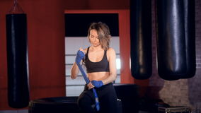 Beauty Thai Boxing woman putting on punching wraps in fitness studio. 4K stock video