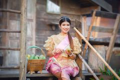 Beauty Thai woman Beautiful Thai girl in traditional dress costume. And Pealing mango in the basket royalty free stock photo
