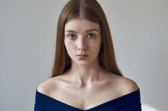 Beauty theme: portrait of a beautiful young girl with freckles on her face and wearing a blue dress on a white background in studi. O shot Royalty Free Stock Image
