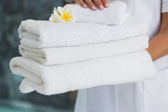 Beauty therapist holding pile of fresh white towels stock image