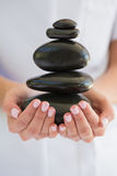 Beauty therapist holding pile of stones for massage stock photos