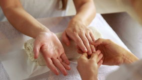 Beauty therapist massaging customers hands stock video