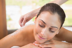 Beauty therapist pouring salt scrub on smiling womans back Stock Photography