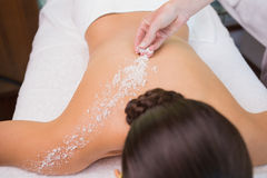Beauty therapist pouring salt scrub on womans back Stock Photo