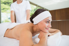 Beauty therapist rubbing smiling womans back with heated mitts Stock Photo