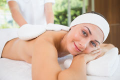 Beauty therapist rubbing smiling womans back with heated mitts Stock Photos