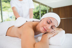 Beauty therapist rubbing smiling womans back with heated mitts Stock Image