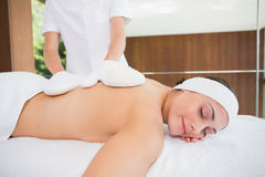 Beauty therapist rubbing womans back with heated mitts Royalty Free Stock Image