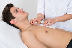 Beauty Therapist Waxing Man's Chest. Close-up Of Beauty Therapist Waxing Young Man's Chest Lying On Bed Royalty Free Stock Image