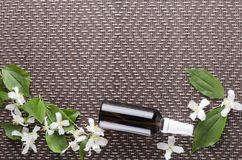 Beauty therapy by using jasmine oil.Spray bottle with jasmine oil on the brown mat, empty space for design. Top view of glass bottle of jasmine oil, empty space royalty free stock photo