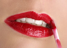 Beauty time. Beautiful young woman applying lipstick Royalty Free Stock Images