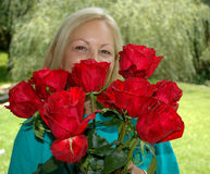 Beauty Times Two. A middle-aged woman peers over a bouquet of beautiful red roses in a suburban home's backyard Stock Image
