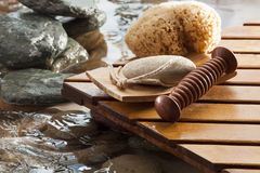 Beauty tools for cleansing process. Natural sponge and massage accessories next to water at the spa Stock Image
