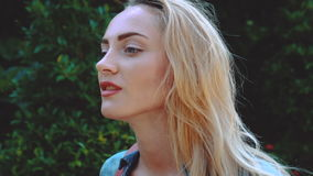 Beauty tourist woman on tropical vacation. Closeup portrait of stunning blond woman in blue denim shirt with light makeup walking in tropical forest during sunny stock video