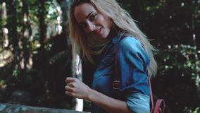 Beauty tourist woman on tropical vacation. Closeup of stunning blond woman in blue denim shirt with backpack looking into the camera and smiling while standing stock footage