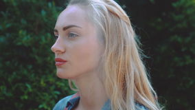 Beauty tourist woman on tropical vacation. Closeup of stunning blond woman in blue denim shirt with light makeup walking with backpack in tropical forest during stock footage