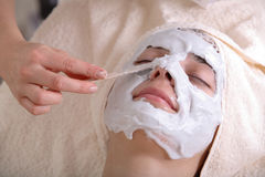 Beauty Treatment. Woman during a beauty treatment of a facial cream being applied to her face stock photo