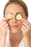 Beauty treatment. Young woman holding cucumber in front of her eyes royalty free stock photography