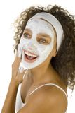 Beauty treatment. Young happy woman with white purifying mask. She's on white background Stock Photography