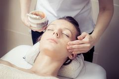 Cosmetician applying facial mask at young woman in spa salon. Beauty treatment concept. Woman relaxing in spa salon. Cosmetician applying facial mask at young stock image