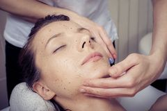 Cosmetician applying facial mask at young woman in spa salon. Beauty treatment concept. Woman relaxing in spa salon. Cosmetician applying facial mask at young royalty free stock photo