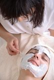 Beauty Treatment Facial. Woman during a beauty treatment of a facial cream being applied to her face royalty free stock photo