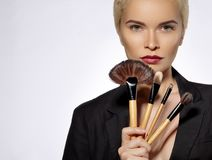 Beauty Treatment. Girl with Makeup Brushes. Fashion Make-up for Sexy Woman. Makeover. Make-up Artist Applying Visage Royalty Free Stock Image