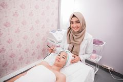 Beauty treatment oxygen therapy. Beautician perform beauty treatment on women face. applying oxygen therapy royalty free stock images