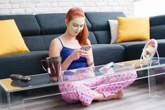 Beauty Treatment Skin Care For Girl Messaging Text On Phone. Girl with beauty mask relaxing at home, messaging text on cell phone. Young woman texting message on Stock Photos