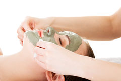 Beauty treatment in spa salon. Woman with facial clay mask. On white stock photography
