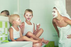 Mother and children make a face mask in the morning.The boys joke with mom. Beauty treatments for the skin. Beauty treatments for the skin.Mother and children stock image