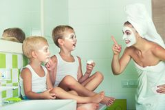 Mother and children make a face mask in the morning.The boys joke with mom. Beauty treatments for the skin. Beauty treatments for the skin.Mother and children royalty free stock images
