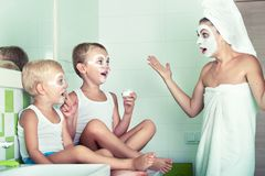 Mother and children make a face mask in the morning.The boys joke with mom. Beauty treatments for the skin. Beauty treatments for the skin.Mother and children royalty free stock photos