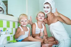 Mother and children make a face mask in the morning.The boys joke with mom. Beauty treatments for the skin. Beauty treatments for the skin.Mother and children royalty free stock photography