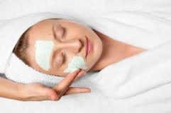 Beauty Treatments. Woman applying facial mask at spa Stock Photos