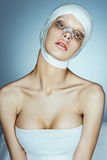 Beauty victim with bandage on her face after facelift. Royalty Free Stock Photography