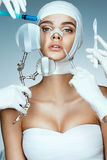 Beauty victim wrapped in medical bandages while doctors with syringes, scalpels and magnifying glass near her face. Beauty concept stock photos