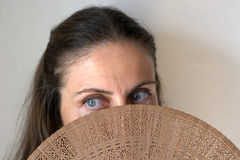 The woman`s gaze behind the sensual fan. The beauty and warmth of Spain and the many traditions Stock Images