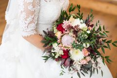 Beauty wedding bouquet in bride`s hands. Two red roses, white dress Stock Images
