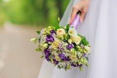Beauty wedding bouquet of violet and white roses. In bride hand Royalty Free Stock Photos