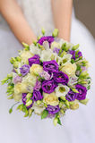 Beauty wedding bouquet of violet and white roses. In bride hands Stock Images