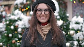 SLOW MOTION: Young woman blowing snow. Young woman blowing snow. Portrait of cute young woman blowing on snow in her stock video footage