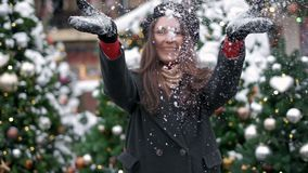 SLOW MOTION: Young woman blowing snow. Young woman blowing snow. Portrait of cute young woman blowing on snow in her stock video