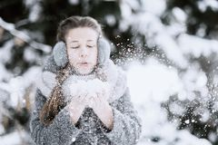 Beauty Winter Girl Blowing Snow in frosty winter Park. Outdoors. Flying Snowflakes. Sunny day stock photos