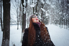Beauty Winter Girl Blowing Snow in frosty winter Park. Flying Snowflakes.  Joyful Beauty young redhead woman Having Fun in Winter Park Royalty Free Stock Photography