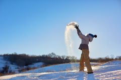 Beauty Winter Girl Blowing Snow in frosty winter Park. Outdoors. Flying Snowflakes. Sunny day. Backlit. Beauty young. Woman Having Fun in Winter Park stock photos