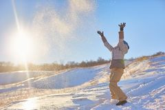 Beauty Winter Girl Blowing Snow in frosty winter Park. Outdoors. Flying Snowflakes. Sunny day. Backlit. Beauty young. Woman Having Fun in Winter Park stock image