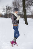Beauty Winter Girl in frosty winter Park. Outdoors. Flying Snowf. Girl playing with snow in park Stock Image