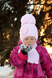 Beauty Winter Little Girl Blowing Snow in frosty winter Park. Flying Snowflakes. Sunny day. Royalty Free Stock Image