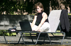 The Beauty of Wireless. A woman sitting in a lawn chair, working on a laptop computer, and enjoying the beauty of wireless technology Royalty Free Stock Images